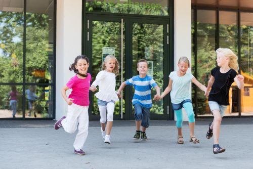 Kinder laufen auf dem Schulhof